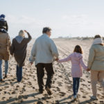 multigenerational family walking on beach for family office wealth management blog