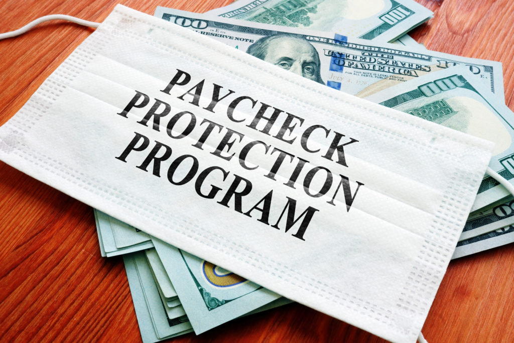 paycheck protection program written on mask with money in the background