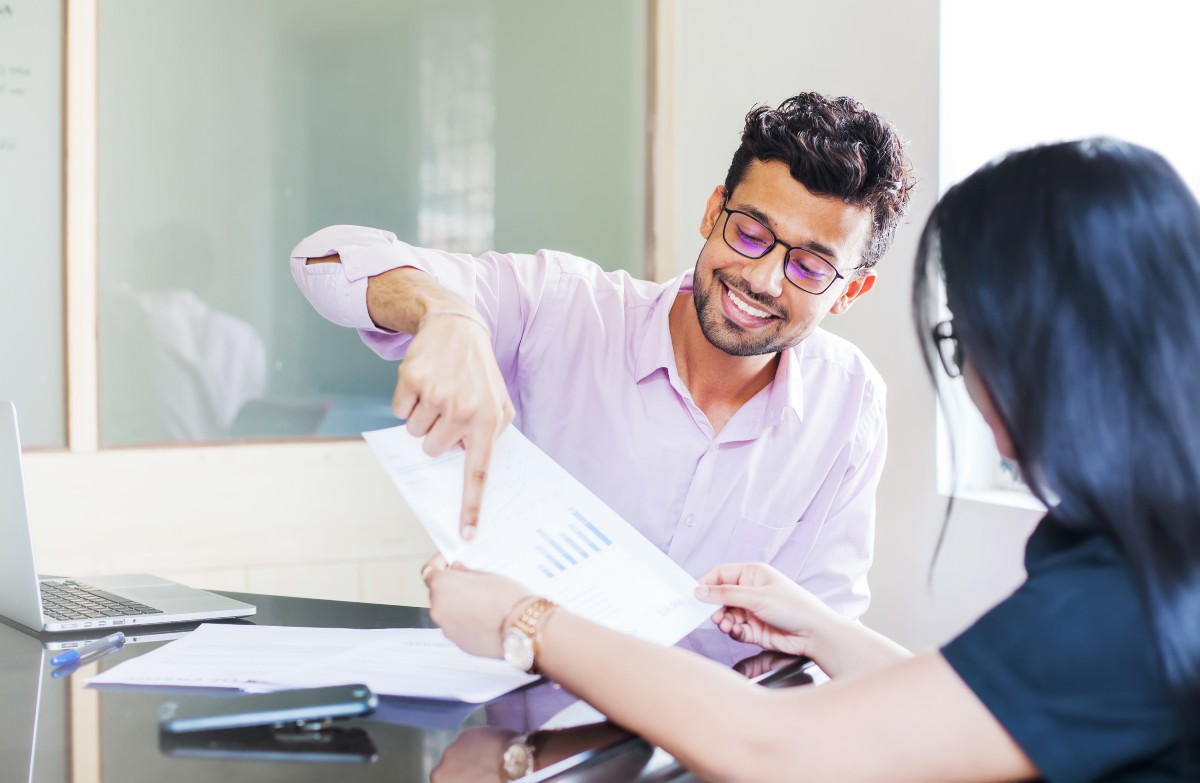 investment strategy - man showing graphs in paper to woman